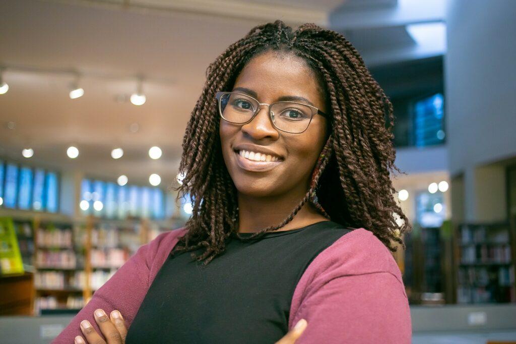 Donkere vrouw-met bril-in bibiotheek