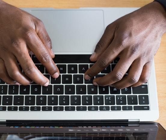 Handen-van-een-zwarte-man-typen-op-laptop